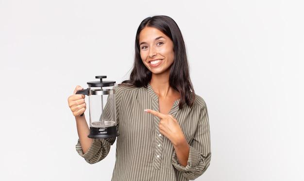 Jovem hispânica sorrindo alegremente, feliz, apontando para o lado e segurando uma cafeteira manual