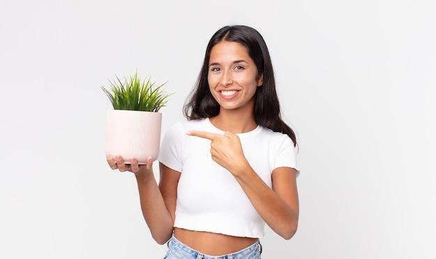 Jovem hispânica sorrindo alegremente, feliz, apontando para o lado e segurando uma planta decorativa na casa