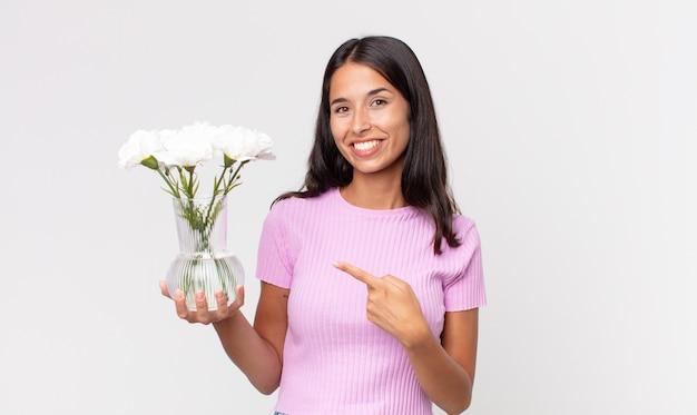 Jovem hispânica sorrindo alegremente, se sentindo feliz e apontando para o lado segurando flores decorativas