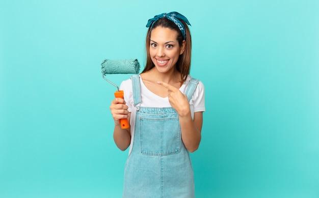 Jovem hispânica sorrindo alegremente, sentindo-se feliz, apontando para o lado e pintando uma parede