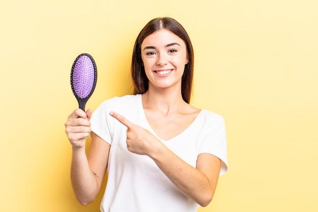 Jovem hispânica sorrindo alegremente, sentindo-se feliz e apontando para o lado. conceito de escova de cabelo