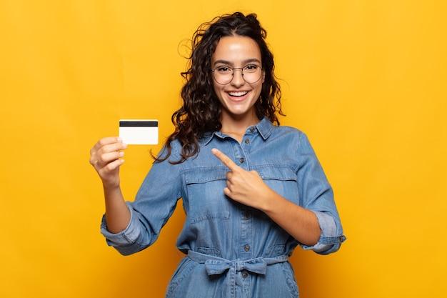 Jovem hispânica sorrindo alegremente, sentindo-se feliz e apontando para o lado e para cima, mostrando o objeto no espaço da cópia