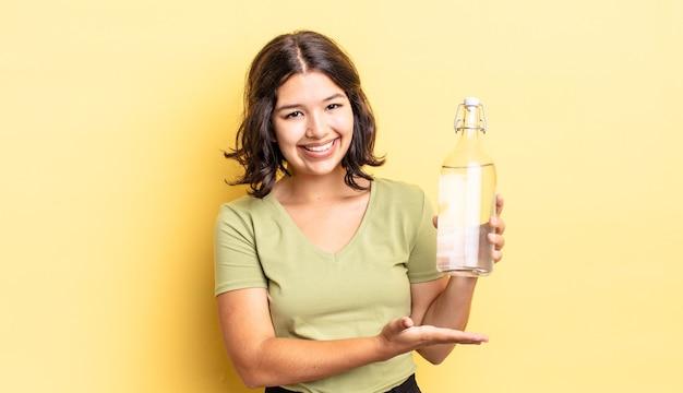 Jovem hispânica sorrindo alegremente, sentindo-se feliz e mostrando um conceito. conceito de garrafa de água