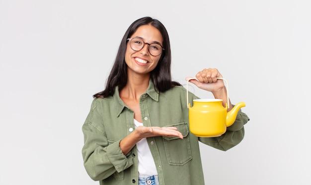 Jovem hispânica sorrindo alegremente, sentindo-se feliz, mostrando um conceito e segurando um bule de chá