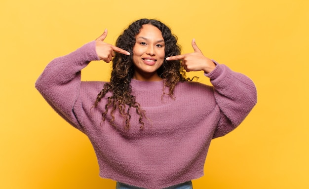 Jovem hispânica sorrindo com confiança apontando para o próprio sorriso largo, atitude positiva, relaxada e satisfeita