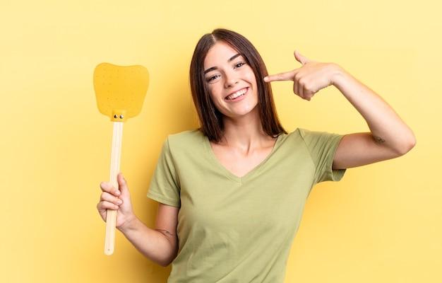 Jovem hispânica sorrindo com confiança, apontando para o próprio sorriso largo. conceito de matar moscas