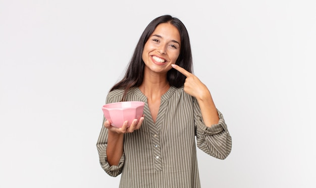 Jovem hispânica sorrindo com confiança, apontando para o próprio sorriso largo e segurando uma tigela ou pote vazio