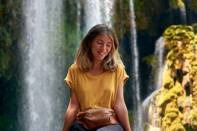 Jovem hispânica sorrindo com os olhos fechados e uma cachoeira ao fundo
