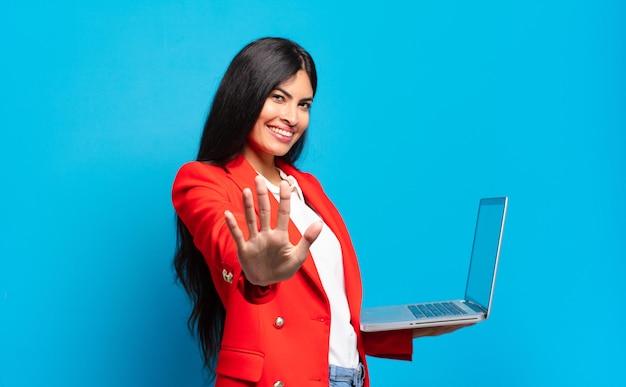 Jovem hispânica sorrindo e parecendo amigável, mostrando o número cinco ou quinto com a mão para a frente, em contagem regressiva. conceito de laptop