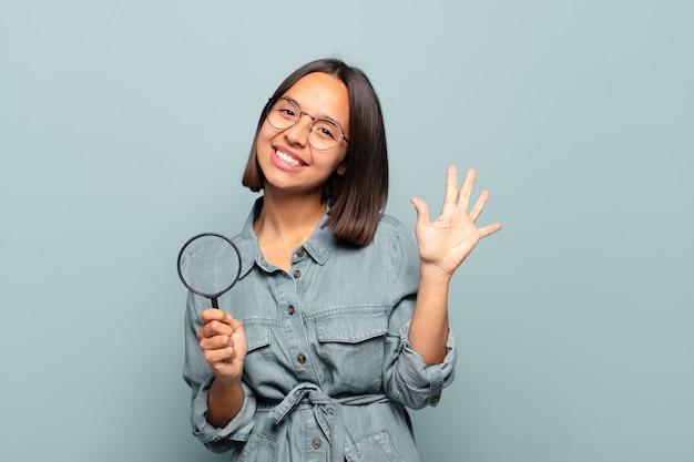 Jovem hispânica sorrindo e parecendo amigável, mostrando o número cinco ou quinto com a mão para a frente, em contagem regressiva