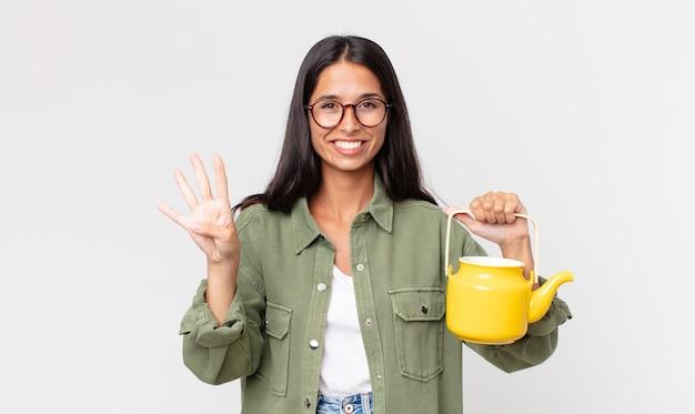 Jovem hispânica sorrindo e parecendo amigável, mostrando o número quatro e segurando um bule de chá