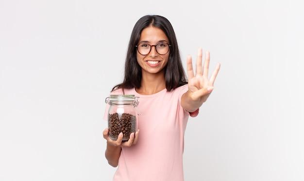 Jovem hispânica sorrindo e parecendo amigável, mostrando o número quatro e segurando uma garrafa de grãos de café Foto Premium