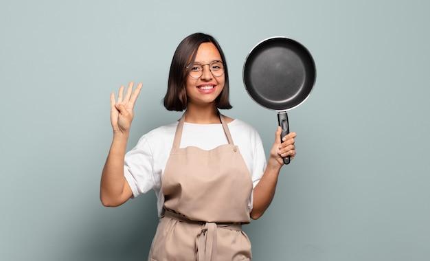 Jovem hispânica sorrindo e parecendo amigável, mostrando o número quatro ou o quarto com a mão para a frente, em contagem regressiva