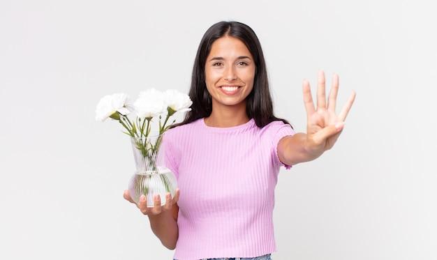 Jovem hispânica sorrindo e parecendo amigável, mostrando o número quatro segurando flores decorativas