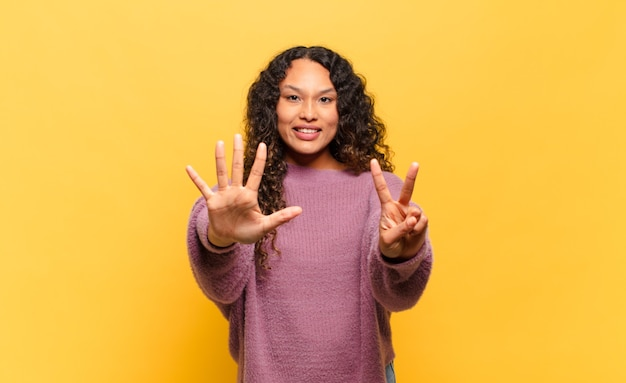 Jovem hispânica sorrindo e parecendo amigável, mostrando o número sete ou sétimo com a mão para a frente, em contagem regressiva