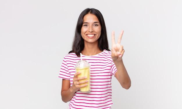 Jovem hispânica sorrindo e parecendo amistosa, mostrando o número dois e segurando um milkshake de vanila smoothy