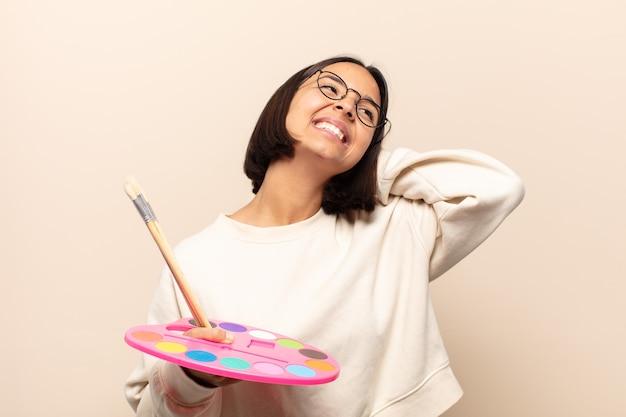 Jovem hispânica sorrindo e se sentindo relaxada, satisfeita e despreocupada, rindo positivamente e relaxando