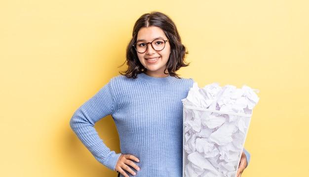 Jovem hispânica sorrindo feliz com uma mão no quadril e confiante falhando no conceito de lixo