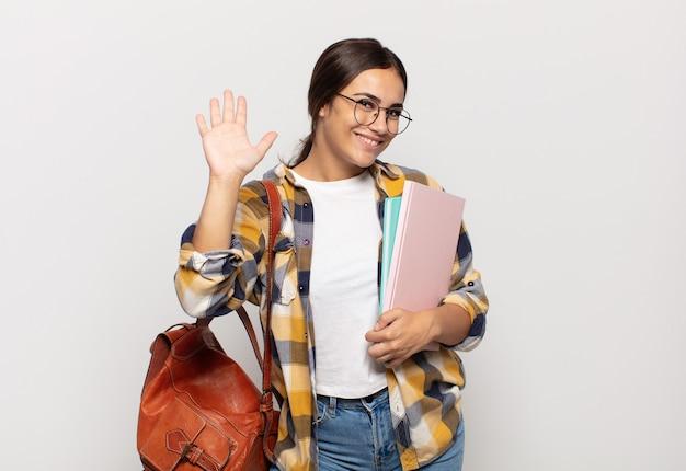 Jovem hispânica sorrindo feliz e animada, acenando com a mão, dando as boas-vindas e cumprimentando você ou dizendo adeus
