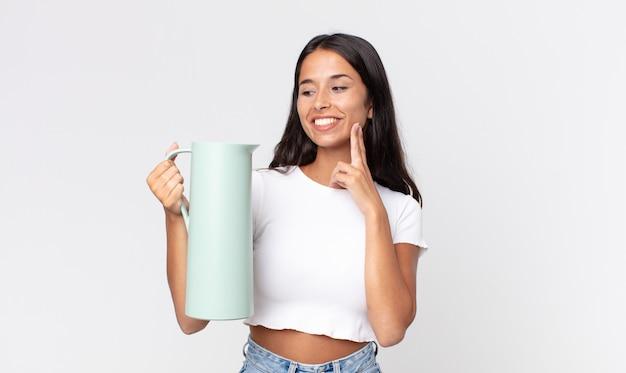 Jovem hispânica sorrindo feliz e sonhando acordada ou duvidando e segurando uma garrafa térmica de café