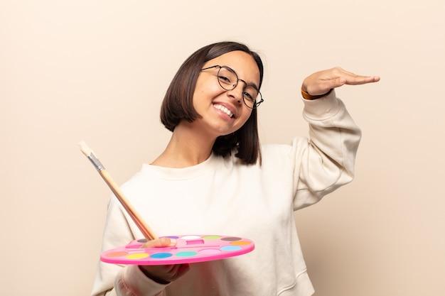 Jovem hispânica sorrindo, sentindo-se feliz, despreocupada e satisfeita, apontando para um conceito ou ideia no espaço da cópia ao lado