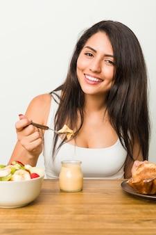 Jovem hispânica tomando café da manhã na mesa