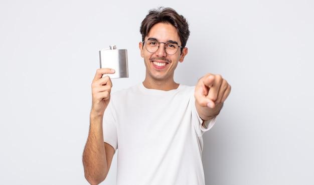 Jovem hispânico apontando para a câmera escolhendo você. conceito de frasco de álcool