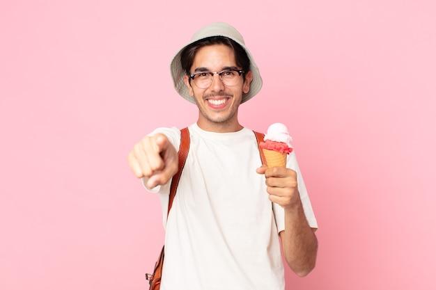 Jovem hispânico apontando para a câmera escolhendo você e segurando um sorvete