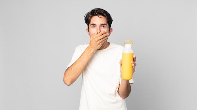 Jovem hispânico cobrindo a boca com as mãos com um choque com uma garrafa térmica de café