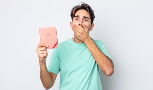 Jovem hispânico cobrindo a boca com as mãos com um choque. conceito de planejador 2022