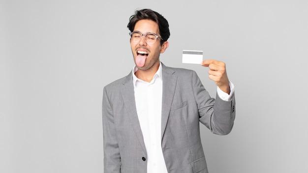 Jovem hispânico com atitude alegre e rebelde, brincando e mostrando a língua e segurando um cartão de crédito