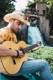 Jovem hispânico com chapéu de cowboy tocando violão em uma paisagem rural