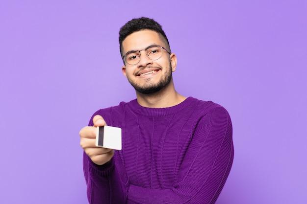 Jovem hispânico com expressão feliz e segurando um cartão de crédito