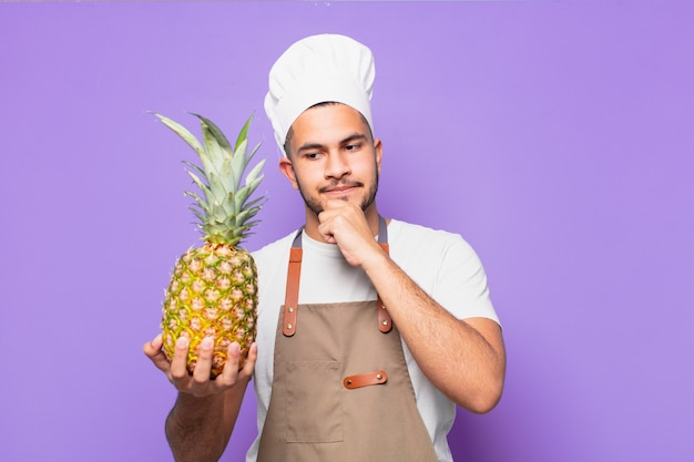Jovem hispânico com expressão pensativa segurando abacaxi
