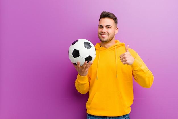 Jovem hispânico com uma bola de futebol contra roxo
