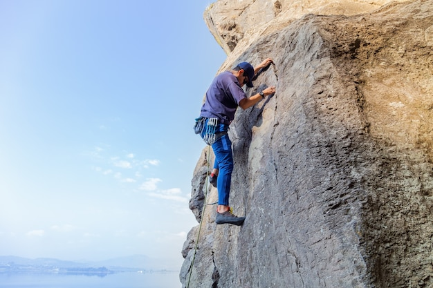 Jovem hispânico com uma corda praticando esportes de escalada na rocha