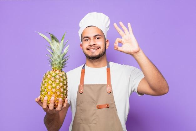 Jovem hispânico com uma expressão feliz segurando um abacaxi