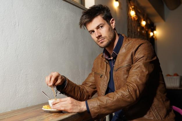 Jovem hispânico com uma jaqueta de couro sentado à mesa e bebendo café