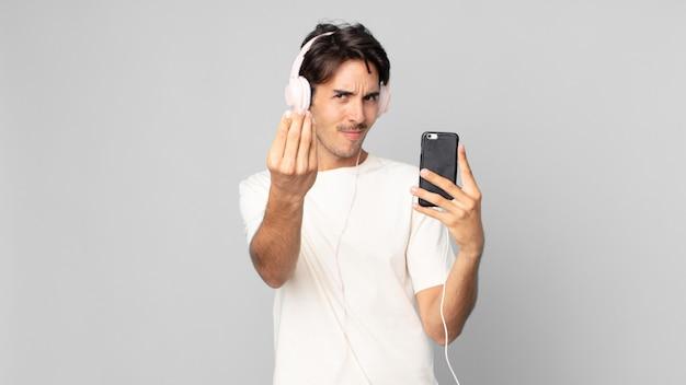 Jovem hispânico fazendo capice ou gesto de dinheiro, dizendo para você pagar com fones de ouvido e smartphone