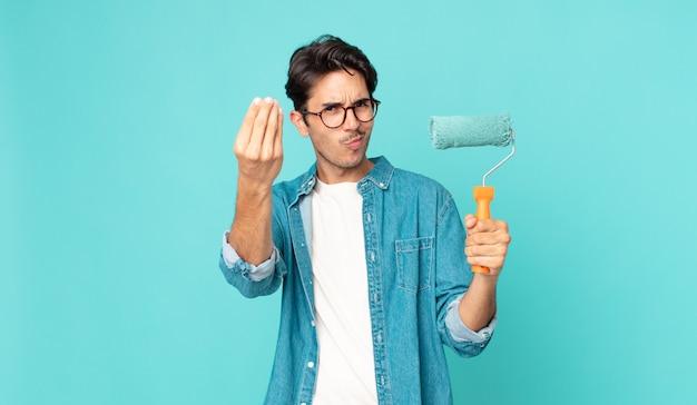 Jovem hispânico fazendo um gesto de capice ou dinheiro, dizendo para você pagar e segurando um rolo de pintura