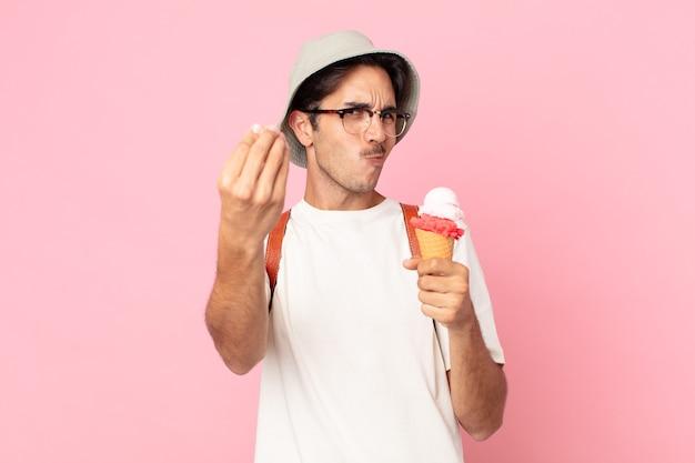 Jovem hispânico fazendo um gesto de capice ou dinheiro, dizendo para você pagar e segurando um sorvete