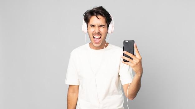 Jovem hispânico gritando agressivamente, parecendo muito zangado com fones de ouvido e smartphone