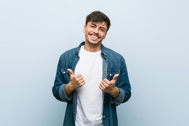 Jovem hispânico legal levantando os dois polegares, sorrindo e confiante.