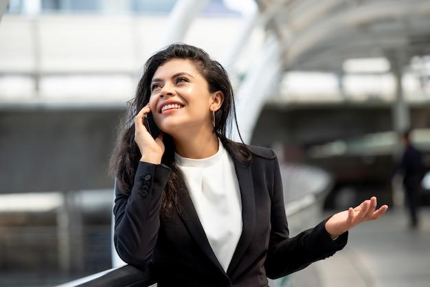 Jovem, hispânico, mulher negócio, falando telefone móvel, ao ar livre