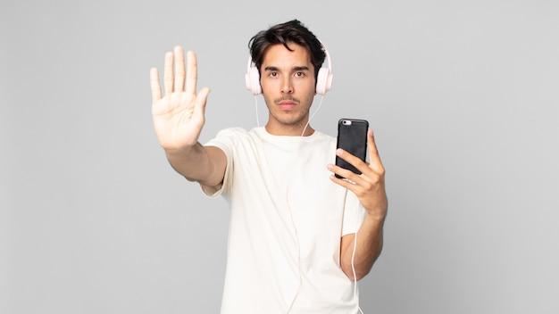Jovem hispânico olhando sério, mostrando a palma da mão aberta, fazendo gesto de parada com fones de ouvido e smartphone