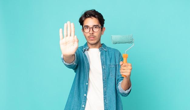 Jovem hispânico olhando sério, mostrando a palma da mão aberta fazendo gesto de pare e segurando um rolo de pintura