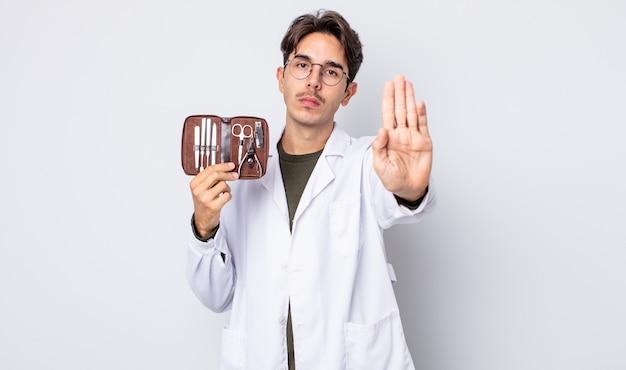 Jovem hispânico olhando sério, mostrando a palma da mão aberta, fazendo o gesto de parada. ferramentas de unhas quiropodistas