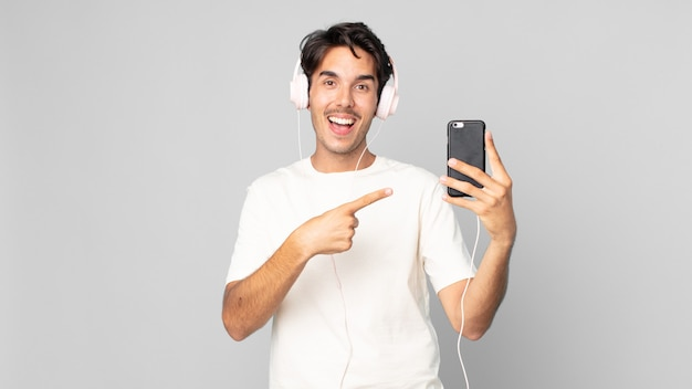 Jovem hispânico parecendo animado e surpreso, apontando para o lado com fones de ouvido e smartphone