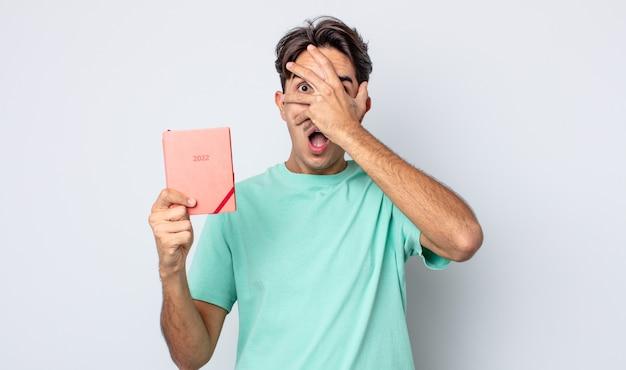 Jovem hispânico parecendo chocado, assustado ou apavorado, cobrindo o rosto com a mão. conceito de planejador 2022