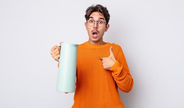 Jovem hispânico parecendo chocado e surpreso com a boca aberta, apontando para si mesmo. conceito de garrafa térmica